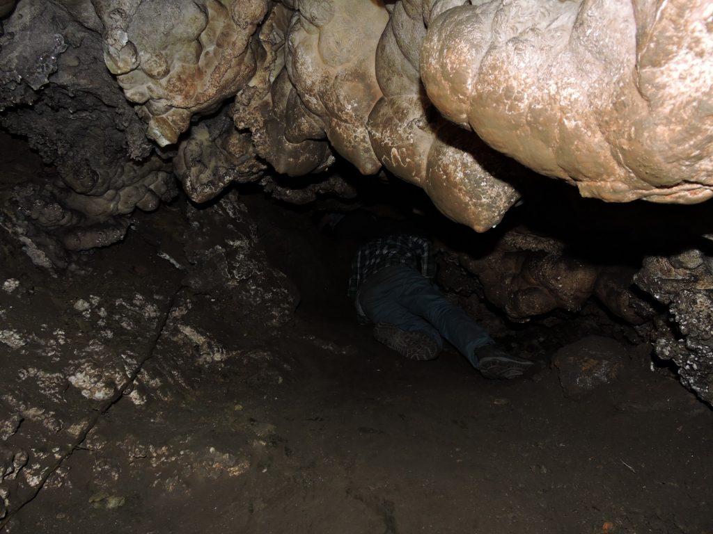 Eksploracja wnętrza jaskini. Uwagę zwraca duża ilość popiołów oraz ślady sadzy (po lewej stronie). Fot. A. Sołtysiak