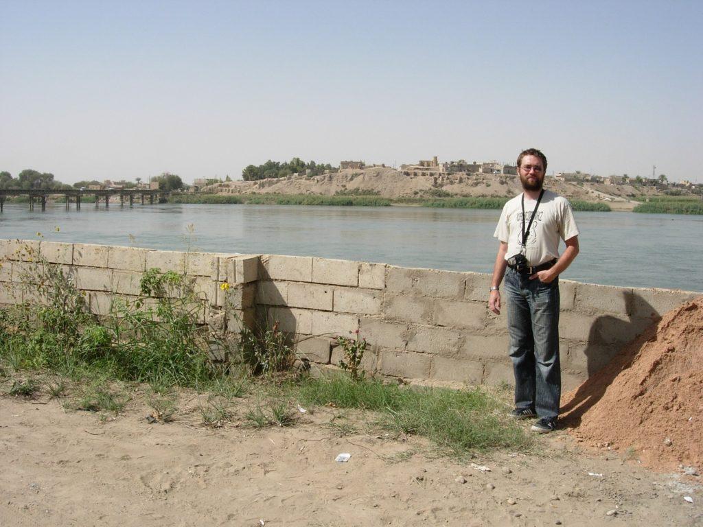 Autor w bazie ekspedycji archeologicznej (rok 2008). W tle widać Eufrat, a na jego drugim brzegu stanowisko Tell Aszara. Ponieważ znajduje się na nim współczesne miasteczko, wykopaliska były możliwe tylko w pobliżu skarpy oraz na placu w pobliżu kępy drzew widocznej po lewej stronie. B. Sołtysiak, zdjęcie na licencji CC BY-NC-SA