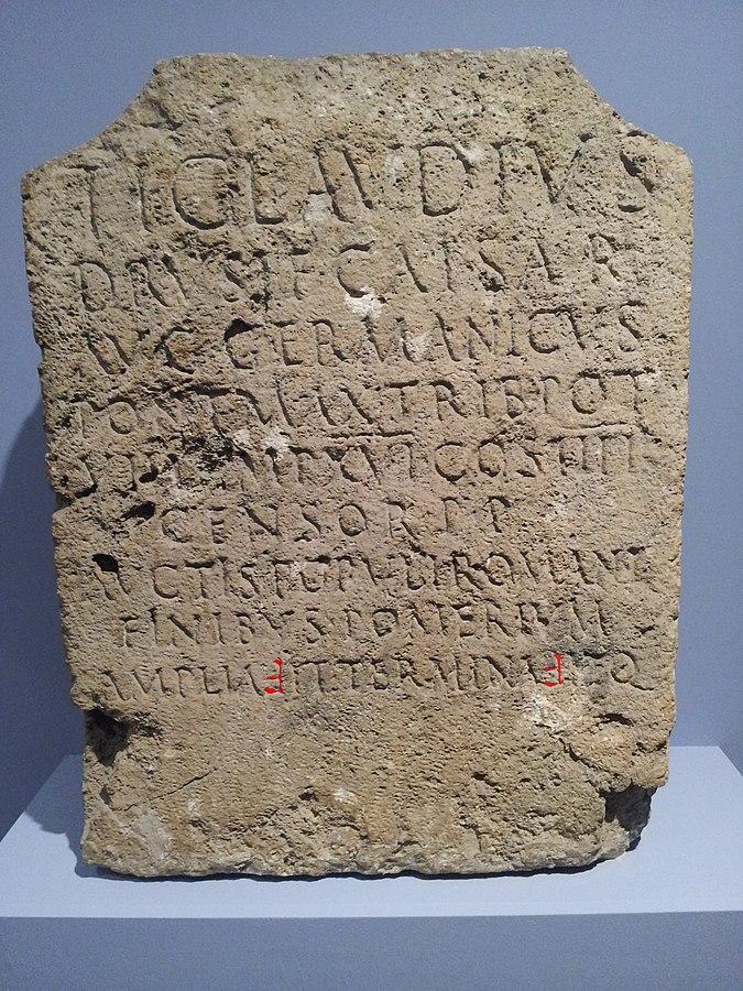 Jeden z kamieni granicznych (cippus)cesarza Klaudiusza, który wyznaczał przedłużenie świętego obwodu miasta Rzymu (pomerium). Przechowywany w Watykanie pod numerem inwentarzowym 9268. Pismo Klaudiusza (odwrócona digamma, tutaj w kolorze czerwonym – zmodyfikowany obraz cyfrowy) zapisuje spółgłoskę V w ampliavit i terminavit. CIL 06, 01231c autor: P. Tribhou (opublikowano na licencji CC BY-SA 4.0, via Wikimedia Commons)
